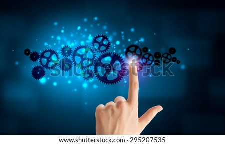 Close up human hand pointing at gears mechanism