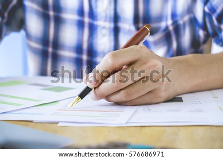 Close up Human Hand Signing contract on Formal Paper at the Table