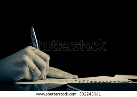 Close up Human Hand Signing on Formal Paper at the Table. Black Background. - stock photo