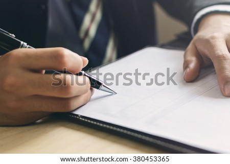 Close up Human Hand Signing on Formal Paper at the workplace