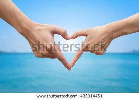 close up human hands gesture heart shape over blurry natural ocean sea background:people love ecology efficiency idea:responsible of world planet life concept:preventive and protection global impact - stock photo