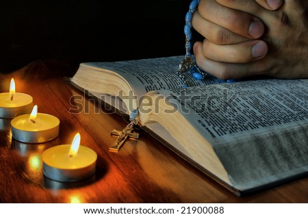 "Close up human hands with rosary on the Bible, and lights on the table in ""HDR"" processing"