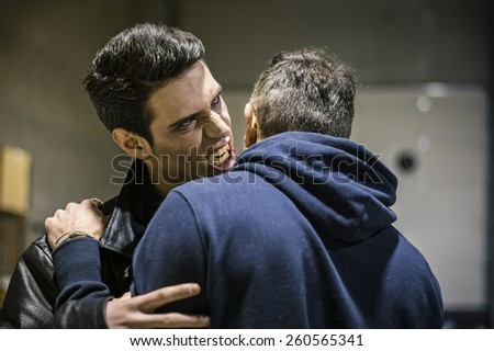 Close up Hungry Young Male Vampire with Scary Facial Expression Bites the Neck While Holding a Man - stock photo