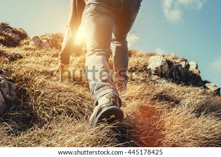Close up imade climber legs make a last steps before peak - stock photo