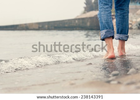 Close up image barefoot man legs in the sea surf - stock photo