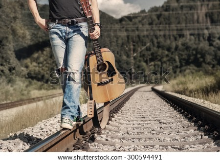 Close up image man legs in ripped denim walk on the railway - stock photo