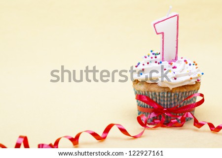 Close-up image number 1 candle on cupcake with red streamer tied over yellow background. - stock photo