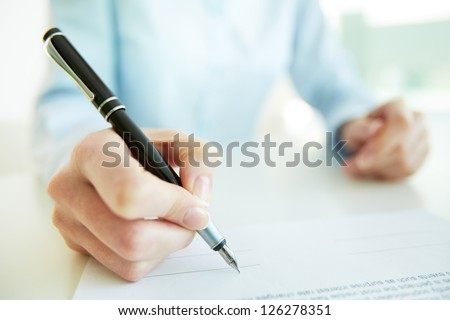 Close-up image of a business woman being to put her signature - stock photo