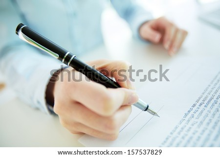 Close-up image of a business woman going to put her signature - stock photo