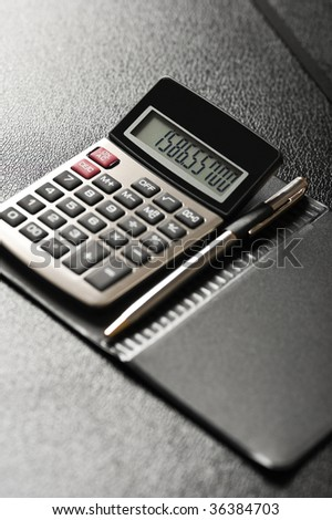 Close-up image of a calculator with a pen on a black background
