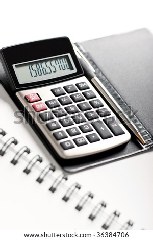 Close-up image of a calculator with a pen on a white background - stock photo