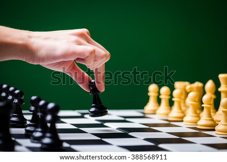 Close-up image of a chess board with chess pieces and a human hand. - stock photo