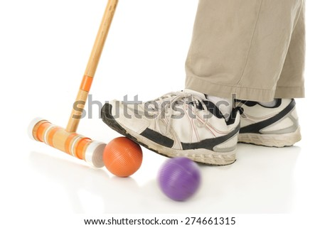Close-up image of a croquet mallet hitting an orange ball under a player's foot to send off an opponent's purple ball.  Motion blur on mallet and purple ball.  On a white background. - stock photo
