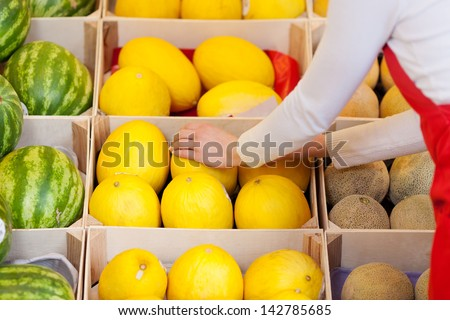 Close-up image of a female worker stacking melons in the supermarket. - stock photo