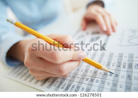 Close-up image of a financial worker analyzing statistical data - stock photo