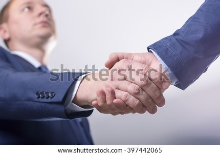 Close-up image of a firm handshake between two colleagues in office