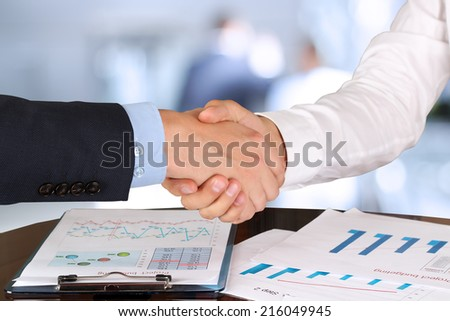 Close-up image of a firm handshake  between two colleagues in  the office. - stock photo
