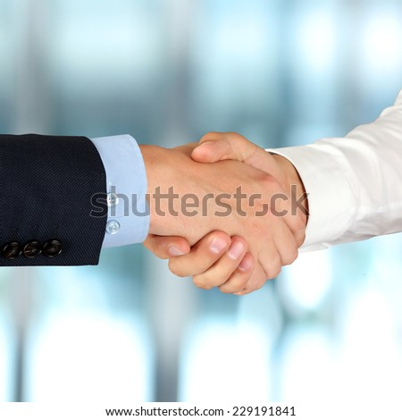 Close-up image of a firm handshake  between two colleagues in  the office.