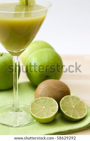 Close-up image of a glass with a green fruit juice and lime and kiwi fruits as decoration.