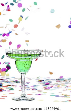 Close-up image of a green drink in martini glass while confetti falling in background. - stock photo