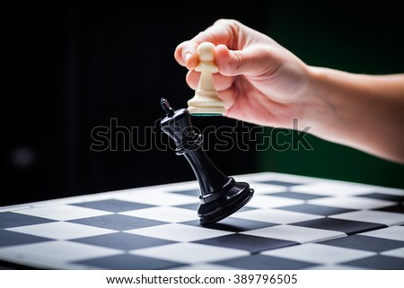 Close-up image of a hand moving a chess piece and defeating the challenger. - stock photo