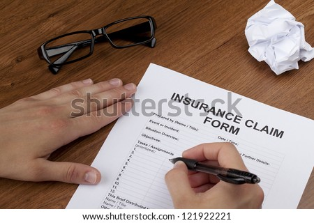 Close-up image of a human hand about to fill up the blank insurance claim form - stock photo
