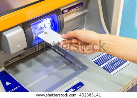 Close up image of a human hand inserting a debit chip card  in the ATM - stock photo