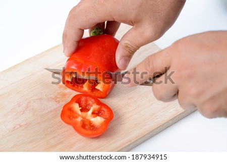 Close-up image of a human hand with knife slicing red bell peppe