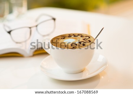 Close-up image of a latte cup with a spoon on a table, a book and eyeglasses on the foreground  - stock photo