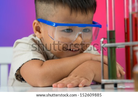 Close-up image of a little boy looking at the chemical substance with interest in the lab - stock photo