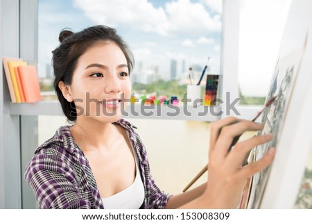 Close-up image of a lovely artist busy with painting on the foreground - stock photo