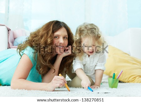 Close-up image of a lovely mom drawing with her little daughter - stock photo