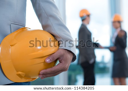 Close-up image of a male worker holding a hardhat, his colleagues can be seen in the background - stock photo