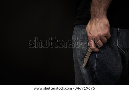 Close up image of a man in jeans and a t shirt holding a pocket knife at his side in front of a black background.