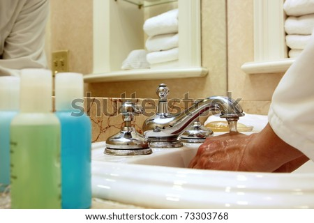 Close up image of a man's hands under a running faucet in a luxury spa or hotel with spa towels and accessories surrounding him (shallow depth of field).