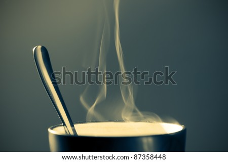 close up image of a mug containing hot beverage on a dark bluish background with vignette