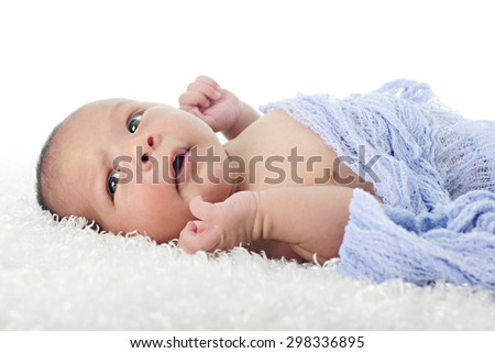 Close-up image of a newborn boy laying on his back swaddled in blue.  He has his eyes wide opened.  On a white background. - stock photo