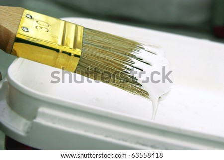 Close-up image of a paint brush with white paint. - stock photo