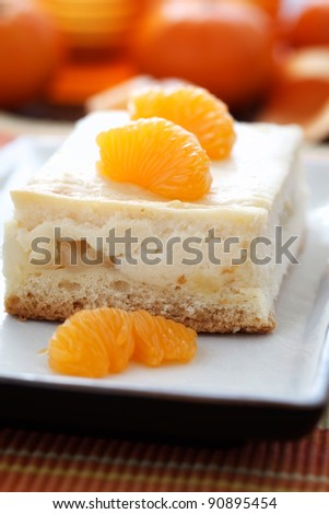 Close-up image of a piece cheese cake with mandarins.