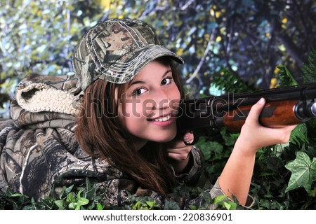 Close-up image of a pretty young teen hunter looking at the viewer as she lays on the ground ready to hit her prey.