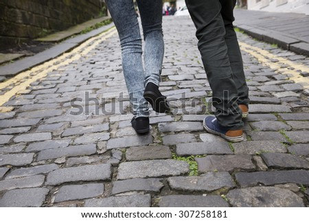 Close up image of a Romantic couple's legs walking down the street in europe. Young man and woman walking together. - stock photo