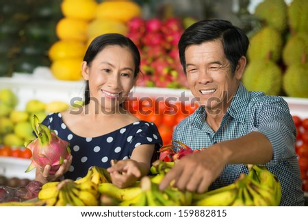 Close-up image of a senior couple buying fruits and vegetables in the market on the foreground - stock photo