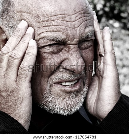 Close up image of a senior man suffering from severe headache - stock photo