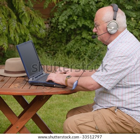 Close-up image of a senior using a laptop outside. headphones voip online internet oap