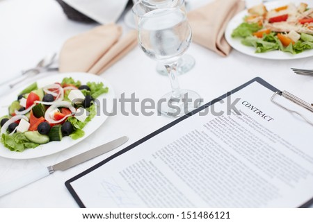 Close-up image of a served lunch with a business contract in the foreground - stock photo