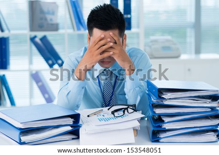 Close-up image of a stressful businessman tired from his work on the foreground  - stock photo