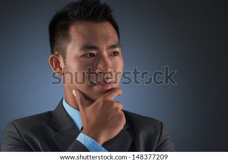 Close-up image of a thoughtful businessman with chin-on-hand against a grey background - stock photo