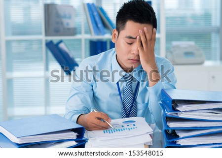 Close-up image of a tired businessman at his workplace among paper documents on the foreground  - stock photo