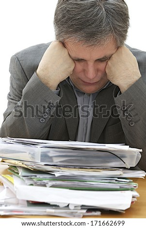 Close-up image of a tired businessman at his workplace among paper documents on the foreground