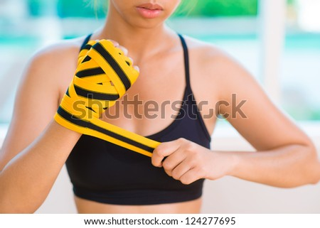 Close-up image of a tough girl taping her hand - stock photo